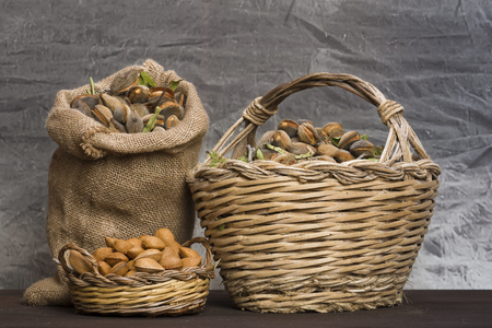 Almonds over a rustic wooden board. Rustic sack and basket. Nutcracker and almond oil. Almond flour. Stock Photo