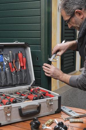 Locksmith repairing a door lock uses the gauge. Archivio Fotografico