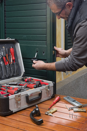 Locksmith repair the lock of a door of the house with a suitcase of tools. Archivio Fotografico