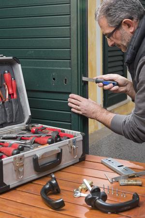 Locksmith repairing a door lock uses the rasp. Archivio Fotografico