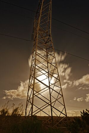 Trellis for transporting electric current in the night with the moon and clouds. Electric Power Transmission Lines