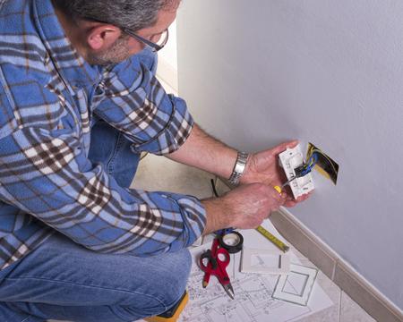 Electrician의 손은 표준 바이폴라 벽 소켓을 조립합니다. 스톡 콘텐츠