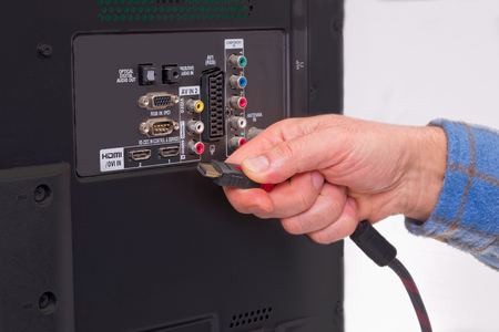 Hand holding cables in the back of an HDTV box. Showing colorful component plug-in area. Stockfoto