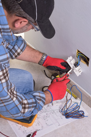 Electrician prepares the conducting cables with insulated scissors to assemble the electrical system. Stock Photo
