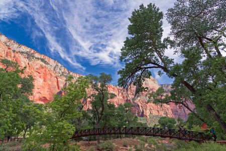 Springdale, Utah, USA - June 3, 2015: A group of tourists, at sunset, cross the bridge over the Virgin River. In the background the wonderful rock formations of the canyon. Zion Park, Utah.