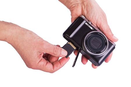 Insert memory card into the camera. Womans hands on a white background.