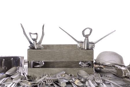 Wooden box filled with stainless steel kitchen cutlery. White cutout background. Foto de archivo
