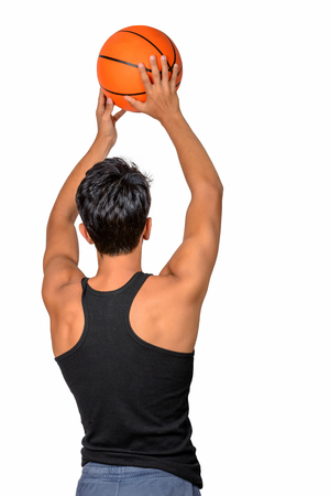 Portrait of a young basketball player passing the ball. Young caucasian boy in sportswear playing basketball on white background with copyspace