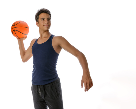 Portrait of a young basketball player passing the ball. Young caucasian boy in sportswear playing basketball on white background with copyspace Archivio Fotografico - 106235275