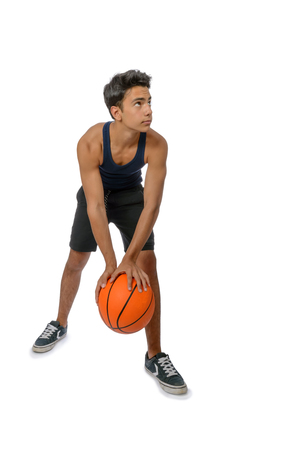 Portrait of a young basketball player passing the ball. Young caucasian boy in sportswear playing basketball on white background with copyspace Archivio Fotografico - 106235187