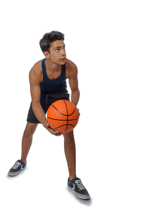 Portrait of a young basketball player passing the ball. Young caucasian boy in sportswear playing basketball on white background with copyspace Archivio Fotografico - 106235189