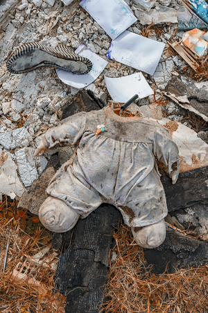 Body of a doll without a head distressing lying in a landfill with other waste. Stock fotó