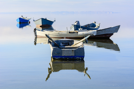 Old wooden fishing boats with bright colors at dawn on the lake. Bright colors: blue, green and yellow. Stock fotó