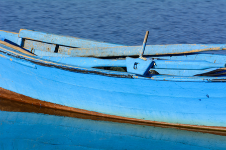 Particular of old wooden fishing boats with bright colors at dawn on the lake. Bright colors: blue, green and yellow.