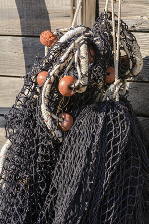 Detail of black fishing net with floats hanging on the old wooden boat.