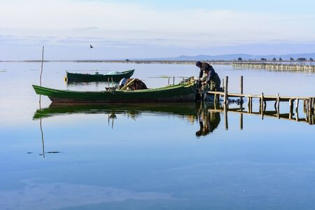Bruncuteula, SantAntioco, Italy - January 28, 2016: Fishermen with their ancient boats, fall at dawn, landscape of the lagoon of SantAntioco in south west Sardinia.