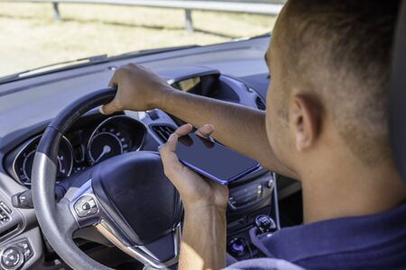Young driver, using smartphone, on the road in the car. Distraction and danger on the road. Stock Photo