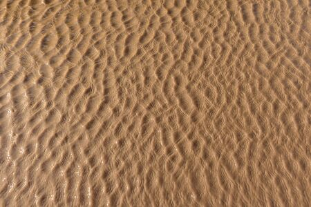 Photograph of small real water waves and reflections for texture. Brown color.
