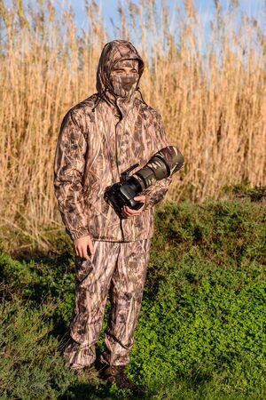 Naturalist photographer in action, with camouflage and camera, in the wilderness. Stock Photo