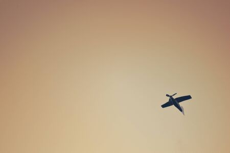 attainment: Small wooden toy plane flies in the sky, creative background