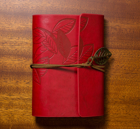 Red notebook with tape on a wooden table