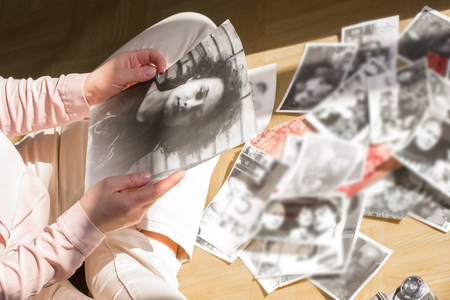 old photograph: Young woman is sitting on the floor and looking at old photographs