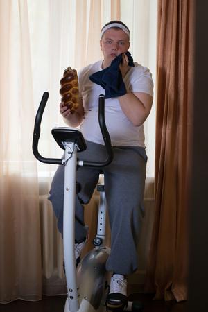 niño parado: Fat guy ejercicio en bicicleta de formación estacionaria y comer un bollo en casa
