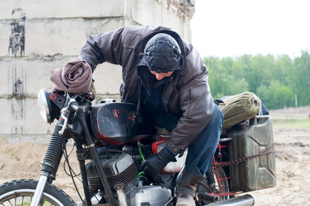 A post apocalyptic man on motorcycle near destroyed building