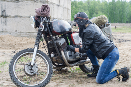 A post apocalyptic woman near motorcycle near destroyed building