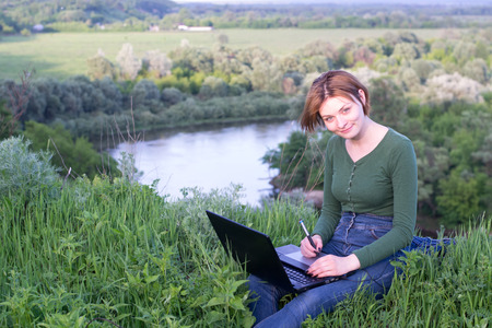 stylus pen: Beautiful girl using her graphic tablet sitting in the grass