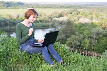 Mooi meisje met behulp van haar grafische tablet zitten in het gras