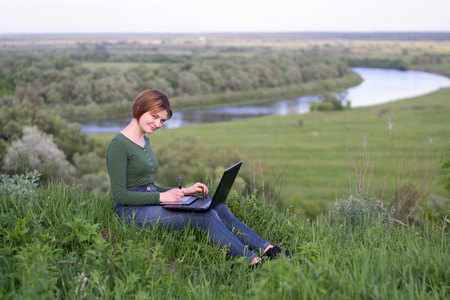 stylus pen: Beautiful girl using her graphic tablet sitting in the grass near river