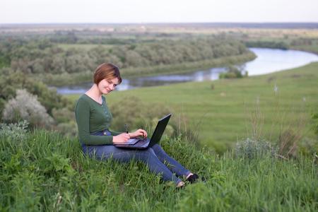 Mooi meisje met behulp van haar grafische tablet zitten in het gras in de buurt van de rivier Stockfoto