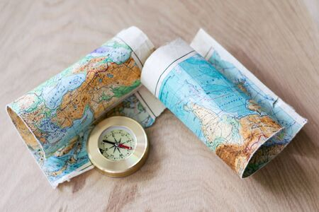 Map and compass lying on wooden background