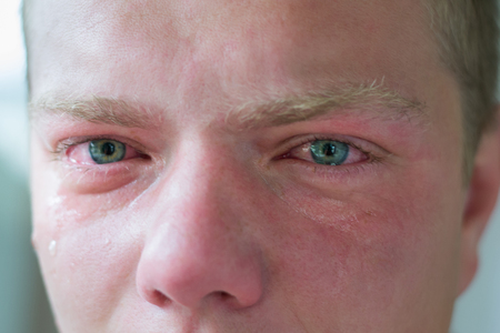 Face of crying man with blue eyes