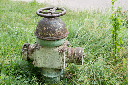 Old hydrant on a background of grass