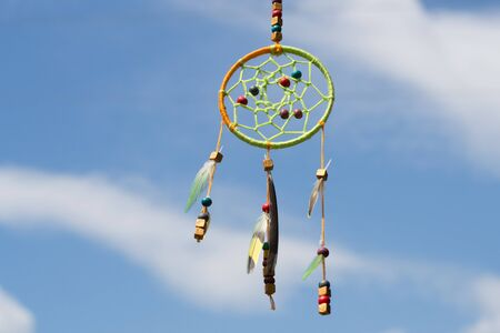 Dream catcher in the wind against the sky