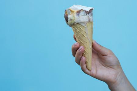 Ice cream cones in the hand on azure background