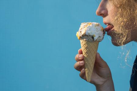 Girl eat ice cream cones on azure background Stock Photo
