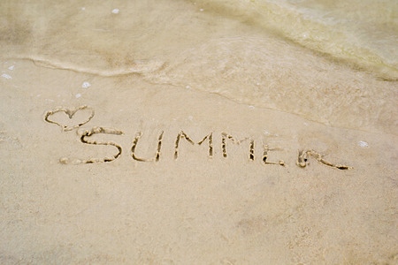 The word summer written on sand, washed with water