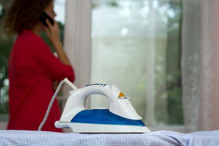Fille parlant au téléphone en oubliant le fer sur la planche à repasser Banque d'images - 83264855
