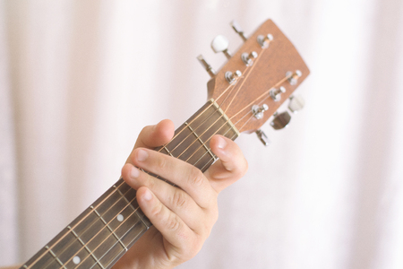 Photo of mans playing tuning guitar, close-up Stock Photo