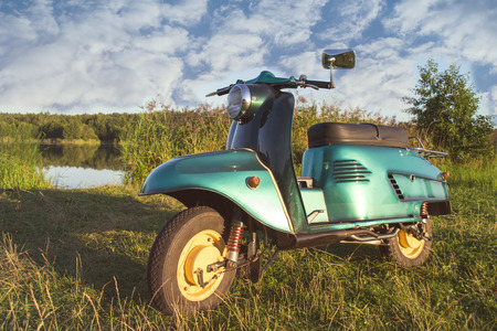 Restored retro motorbike standing on a meadow in the afternoon Stock fotó