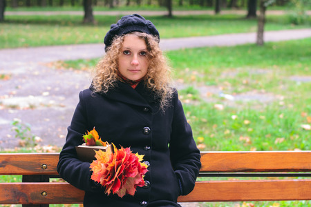 guardar silencio: Girl in a black coat holding maple leaves and a book in the park in autumn