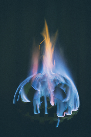 Scary halloween pumpkin burning with blue flame on a black background Stock Photo