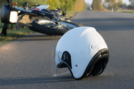 Photo of helmet and motorcycle on road, the concept of road accidents Stok Fotoğraf - 88932018