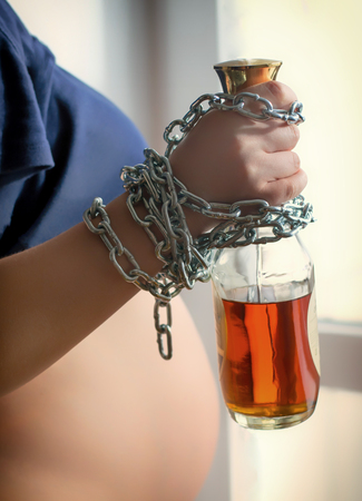 Hand of of a pregnant woman chained with a bottle of alcohol