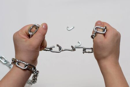 Photo of hands holding a broken mettalic chain Stock Photo
