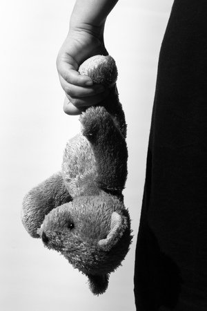 Black and white photo of a girl holding a teddy bear, theme of social problems