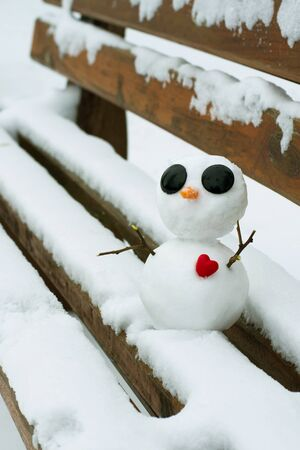 Little snowman with a red heart on a snowy bench 스톡 콘텐츠